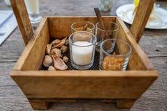 Der Weinleseholzkistekorb, der Zuckergläser halten und der Löffel für Kaffee und Tee mit Meer schälen Dekoration auf Holztisch Lizenzfreies Stockbild