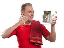 Der well-groomed Mann benutzt Balsam, nachdem er rasiert hat Lizenzfreie Stockfotos