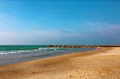 Der Wellenbrecher, der vom Strand in das Meer verlängert stockbild