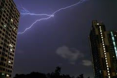 Der wirkliche Blitz, der im nächtlichen Himmel über Hochhäusern von Bangkok blitzt Stockfotos
