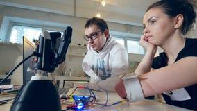 Der Wissenschaftler und das behinderte Mädchen versuchen, die Roboterhand herzustellen, um den Bewegungen der amputierten Hand zu stock video