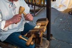 Der Woodcarver, der im Volkskostüm gekleidet wird, schnitzt vom Holz stockfotografie