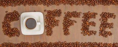 Der Wort Kaffee buchstabierte mit Hunderten von den Kaffeebohnen und von einem Cu stockbild
