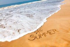Der Wort-Sommer geschrieben in den Sand auf einen Strand mit Zeichnung von t Lizenzfreie Stockfotografie