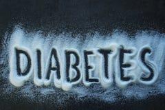Der Wortdiabetes geschrieben in einen Stapel des granulierten Zuckers des Weiß Stockfotos