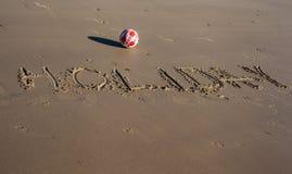 Der Wortfeiertag geschrieben auf den Sand eines Strandes Lizenzfreies Stockbild