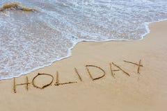 Der Wortfeiertag im Sand des Strandes geschrieben mit Wellen der Brandung stockfotografie