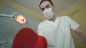 Der Zahnarzt überprüft den Mund unter Verwendung der Werkzeuge Gesichtspunkt des Patienten im Stuhl stock footage