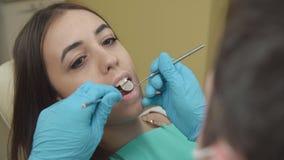 Der Zahnarzt überprüft einen weiblichen Patienten im zahnmedizinischen Büro stock footage