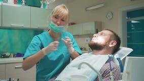 Der Zahnarzt, der geduldige ` s Zähne überprüft, erklärt ihn Verfahren Schieberschuß, Recht stock video footage