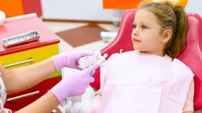 Der Zahnarzt unterrichtet das kinder- ein kleines nettes Mädchen ohne vordere Milchzähne, wie man die Zähne säubert, die in einem stock footage