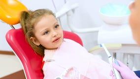 Der Zahnarzt unterrichtet das kinder- ein kleines nettes Mädchen ohne vordere Milchzähne, wie man die Zähne säubert, die in einem stock video footage