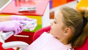 Der Zahnarzt unterrichtet das kinder- ein kleines nettes Mädchen ohne vordere Milchzähne, wie man die Zähne säubert, die in einem stock video
