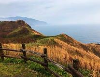 Der Zaun, der Hügel, die Wolke und das Meer Lizenzfreie Stockfotos