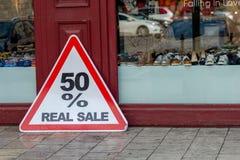Der Zeichen 50% WIRKLICHE VERKAUF am Shopfenster Lizenzfreie Stockfotografie