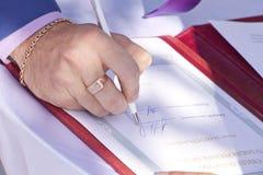 Der Zeuge unterzeichnet das Dokument an der Hochzeit Lizenzfreies Stockbild