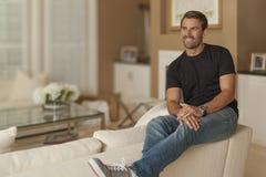 Der zufällig gekleidete Mann genießt einen Moment allein in seinem Wohnzimmer lizenzfreie stockfotografie
