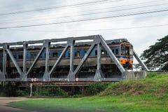 Der Zug läuft auf einer Flussbrücke Stockbild