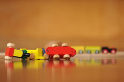 Derailed toy train. Cars of a toy train laying on their sides on a reflective surface with an amber background stock photography