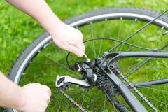 Το άτομο ρυθμίζει το ποδήλατο derailleur Στοκ Εικόνες
