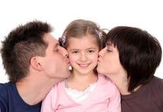 deras kyssande föräldrar för dotter Arkivbilder
