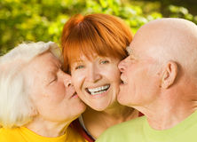 deras kyssande föräldrar för dotter Arkivfoto