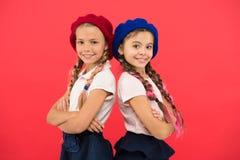 Deras perfekta stil Modeflickor med bundet hår i flätade trådar Franska stilflickor Gulliga flickor som har den samma frisyren arkivfoton