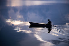 Derawan, Indonesia. A boy rowing his boat during sunrise Royalty Free Stock Photos