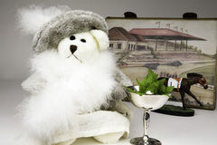 Derby Day. Teddy bear dressed in Derby finery with a silver mint julep cup in front of a race track drawing and a racing bobblehead horse royalty free stock images