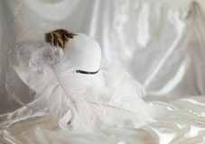 Derby hat with feathers. Derby hat sitting on sateen base with feathers and ribbons royalty free stock photography