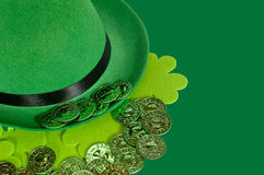 Derby hat on green with shamrocks and coins. St. Patrick's Day background Stock Photos
