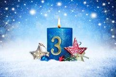 Derde zondag van komst blauwe kaars met de gouden rode decoratie van het metaalaantal op houten planken in sneeuwvoorzijde van zi stock fotografie