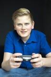 Derecho opinión el muchacho que juega a un videojuego Fotografía de archivo