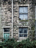 Derelict abandoned house with broken windows and ivy growing up Royalty Free Stock Image
