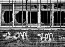 Derelict building. Grafitti covered derelict building with bars at the windows stock image