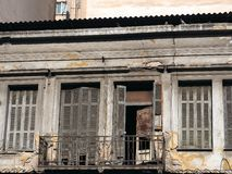 Derelict Building, Athens, Greece. A derelict neoclassical building in Athens` central markets and commercial precinct, with wooden shutters, flaking stucco or royalty free stock images