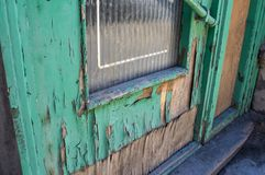 Damaged old green door. Old Retro Green Door Weathered with wood and peeling paint  due to water damage Royalty Free Stock Image