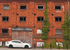 Derelict building with luxury car and pigeon. Old derelict harbourside warehouse with new car parked outside Royalty Free Stock Photography