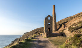 Derelict Cornish tin mine, on the cliff edge, against a blue sky Royalty Free Stock Photo