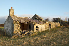 Derelict cottage. Derelict abandoned building, cottage, with crumbling walls and roof on grass with a blue sky Stock Images