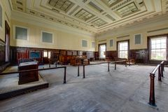 Derelict Courtroom - Abandoned Courthouse, Massachusetts. A view of a derelict courtroom with classical styling at an abandoned courthouse in Massachusetts Stock Photo
