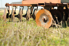 Derelict farm machinery. Close up of derelict agricultural cutting machinery on field Stock Images