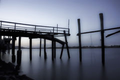 Derelict fishing jetty at dusk. Old wooden fishing jetty moody blue atmosphere Royalty Free Stock Image