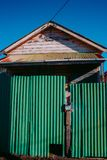Derelict house behind green fence. Derelict weatherboard house behind green fence, against a clear blue sky stock photo