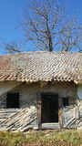 Derelict house in Transylvania. Abandoned wood and tiled house in Transylvania, Romania, fallen into disrepair and dereliction, blue sky background royalty free stock photos