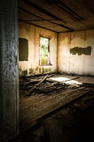 Derelict Interior. Derelict room with window looking out on overgrown area Stock Photo