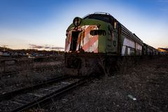 Derelict Locomotive at Twilight - Abandoned Railroad Trains. A view of a derelict locomotive at twilight at an abandoned train railroad yard in Ohio stock images
