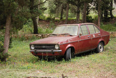 Derelict old car abandoned in Greece. An old Ford escort abandoned and left derelict to rust in pine woodland in Zante, Greece Royalty Free Stock Photo