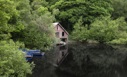 Derelict old retro boathouse and rowing boats hidden in forest l Stock Photos
