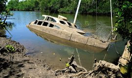 Derelict partially sunken boat in a creek Stock Images